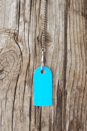 blank blue tag on with silver chain old wooden background Stock Photo - 16542213