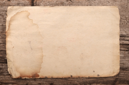 torned: Weathered old paper on a wooden background  Stock Photo