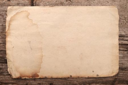 worn paper: Weathered papel viejo en un fondo de madera Foto de archivo