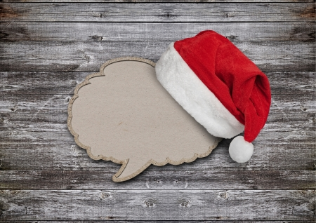 blank recycled paper speech bubble with Santa hat on wood background  photo