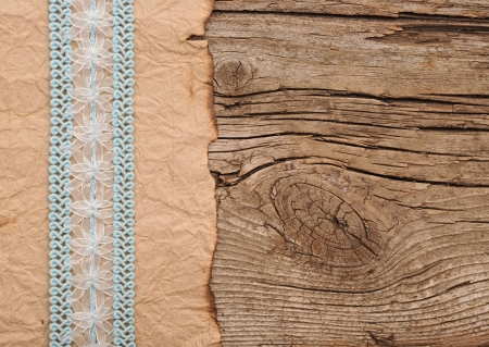 old paper with beautiful ribbon on brown wood texture photo