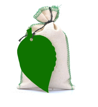 hessian bag with green blank tag in form leaf isolated on white. eco concept  photo