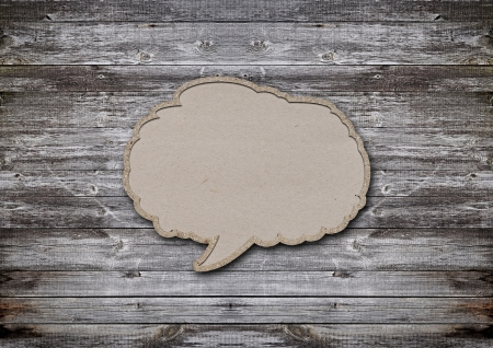 blank recycled paper speech bubble on wood background Stock Photo - 16898560