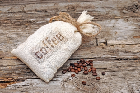 Canvas bag with coffee beans on rustic table with wooden texture  photo