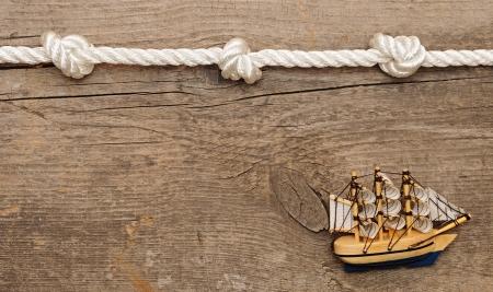 fixed line: cuerda y barco modelo cl�sico en el fondo de madera Foto de archivo