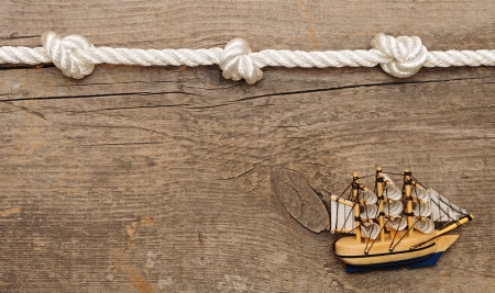 rope and model classic boat on wood background  photo