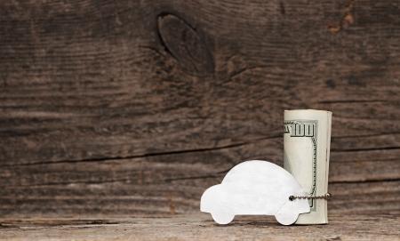 model auto met zilveren ketting over een heleboel dollarbiljetten op oud hout achtergrond. ruimte voor uw tekst