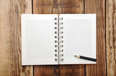 A open note book with pencil on a wooden desk  photo