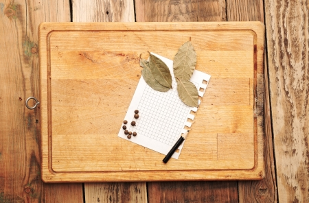 notebook with pencil to write recipes on the background of a cutting board with spices photo