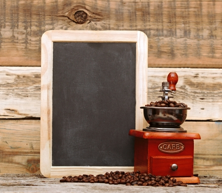 coffee mill and blank chalkboard over wooden background photo