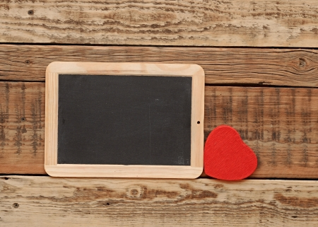 small blackboard  with a red heart on wooden wall photo