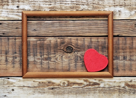 A red heart in an old wooden frame on an old rough wall.  Stock Photo - 17668027