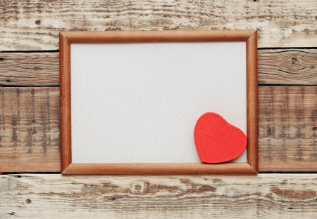 A red heart in an old wooden frame on an old rough wall. Stock Photo - 17668024