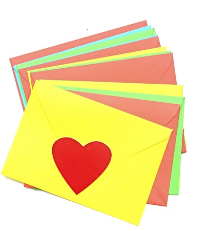 A red heart on pile colorful envelopes over white background photo
