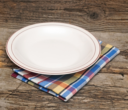 Empty plate on tablecloth on wooden table Stockfoto