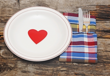 Empty dish, knife and fork and colorful napkin on wood table  photo