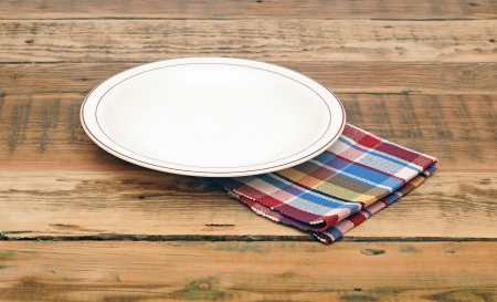 Empty white plate on wooden table  photo