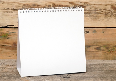 blank desk calendar on wooden table photo