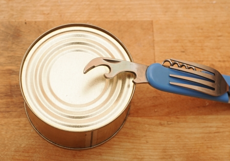 The old tin opener opening a can on wooden table Stock Photo - 17784118