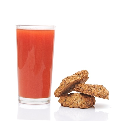 tomato juice glass with cookies isolated on white background photo