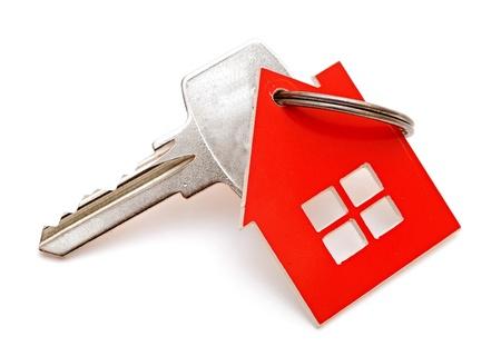 investment real state: Llavero con forma de casa aislada en el fondo blanco
