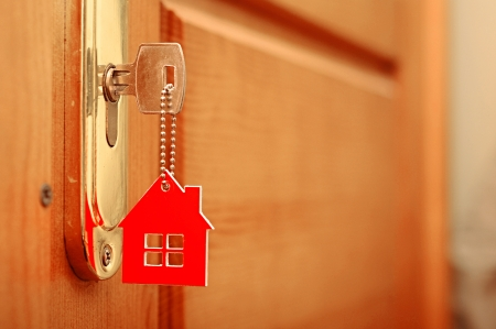 home owner: Symbol of the house and stick the key in the keyhole