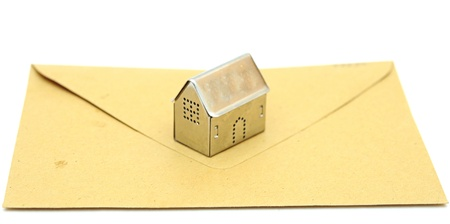 metall: metall house shaped object on brown envelope Stock Photo