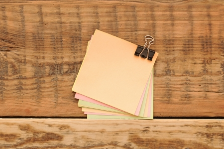 blank color stickers and paper clips on wooden table photo