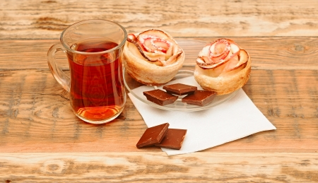 Apple cakes with cup of tea like flower on wooden table photo