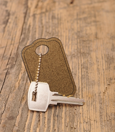 silver key with blank tag wooden background. space for your text photo