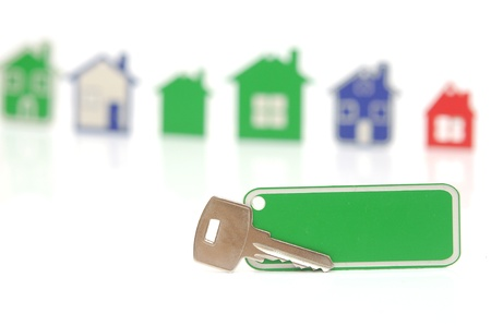 silver key with blank label over the houses background. Space for your text photo