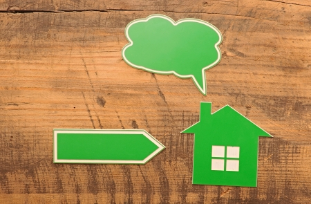 home icon with blank bubble speech and arrow over wooden background