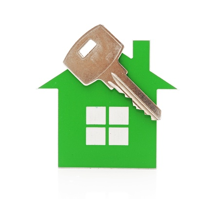 Keychain shaped like a house with a key on a white background. space for your text photo