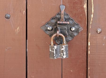Old padlock on a wooden door  Stock Photo - 18668613