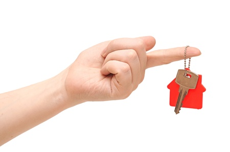 key with red home shape on chain in hand on white background photo