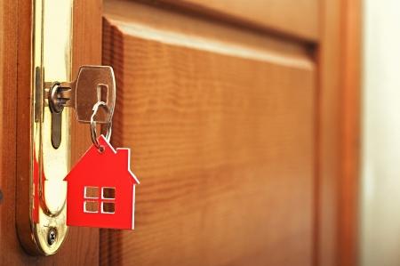 puerta abierta: Una llave en una cerradura con el icono de casa en i