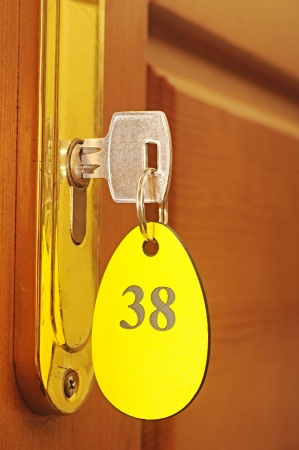 Door handles on wood wing of door and key in keyhole with numbered label  photo