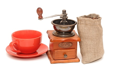 red cup with coffee beans and old coffee mill photo