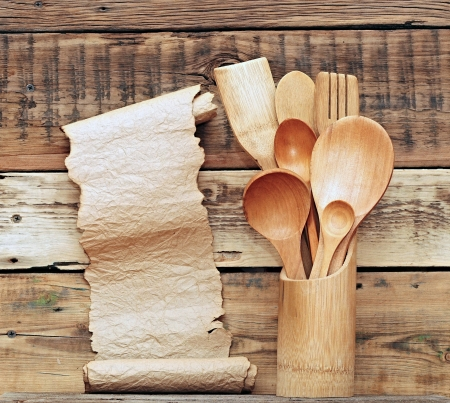 Kitchen wooden utensils in retro bucket with blank paper scroll over wooden background  photo