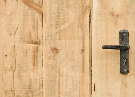 Modern style door handle on natural wooden door  photo