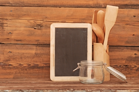 blank blackboard on wooden surface and wooden utensils photo