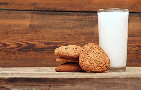 glass of milk and oat cookies on wooden background, close-up  photo
