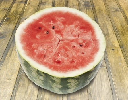 Side view of red watermelon with black seeds on vintage wood table  photo