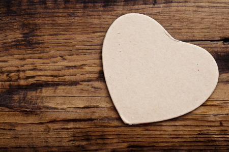 tag in the shape of heart on the wooden background photo
