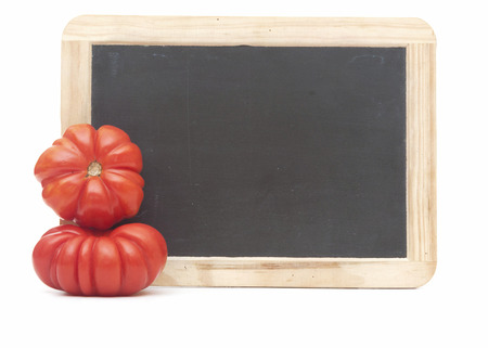 blank blackboard with two ripe tomatoes isolated on white background.  photo