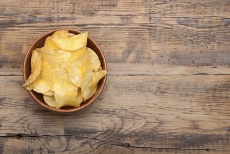 flatfoot: Cheese and chive potato crisp snack in brown bowl on wooden background