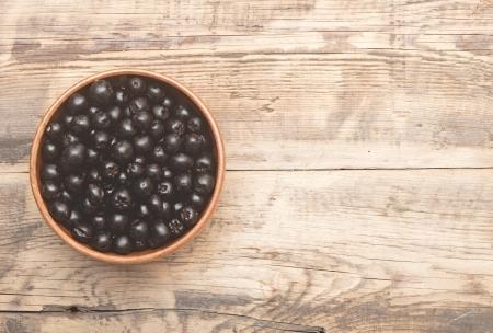 Aronia nero in marrone ciotola sul tavolo in legno Archivio Fotografico - 22664475