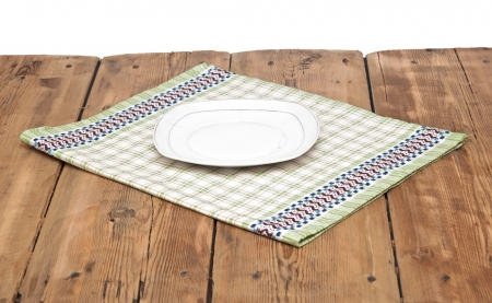 Empty plate on tablecloth on wooden table  photo