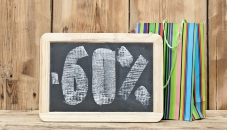 sixty percent discount written on blackboard with colorful shoping bag  photo