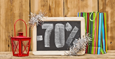 seventy percent discount written on blackboard with christmas decoration photo